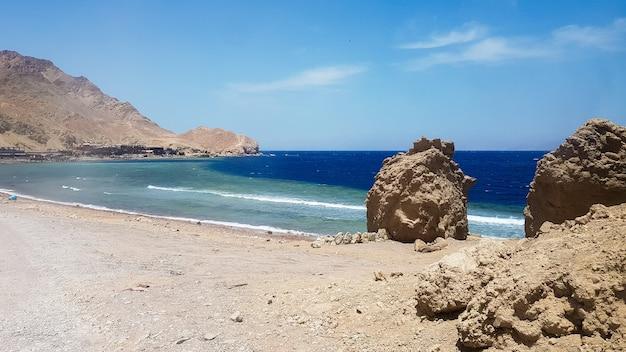 Голубая дыра - популярное место для дайвинга на восточном синае. солнечный берег на берегу красного моря в дахабе. известное туристическое направление недалеко от шарм-эль-шейха. яркий солнечный свет.