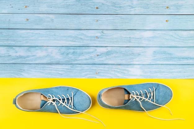 파란색 신발은 격리된 파란색과 노란색 혼합 배경에 서 있습니다