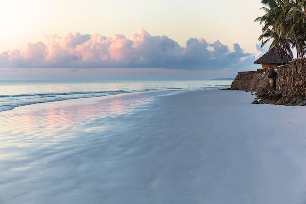 Голубое небо в свете восходящего солнца или заката над морем. отражение солнца
