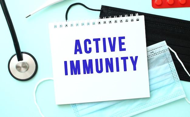 파란색 텍스트 active immunity는 의료 마스크 옆 파란색 배경에 있는 노트북에 쓰여 있습니다