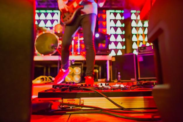 舞台照明を使った抽象的なコンサートでのロックミュージシャンのぼやけたイメージ。抽象的なロックバンドのコンサート