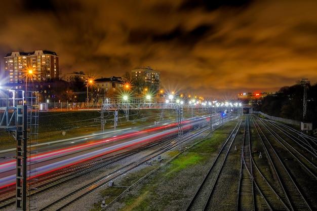 도시의 밤에 철도 선로를 따라 거리로 돌진하는 기차에서 흐릿한 빨간색 선