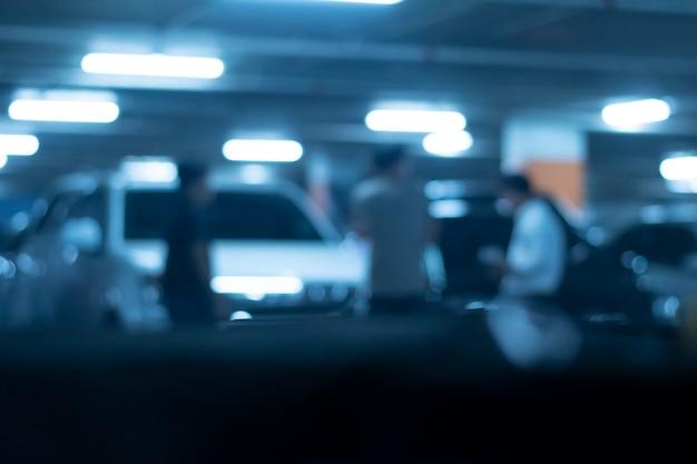밤에 주차장의 이미지가 흐릿하고 사람들이 서 있었습니다.