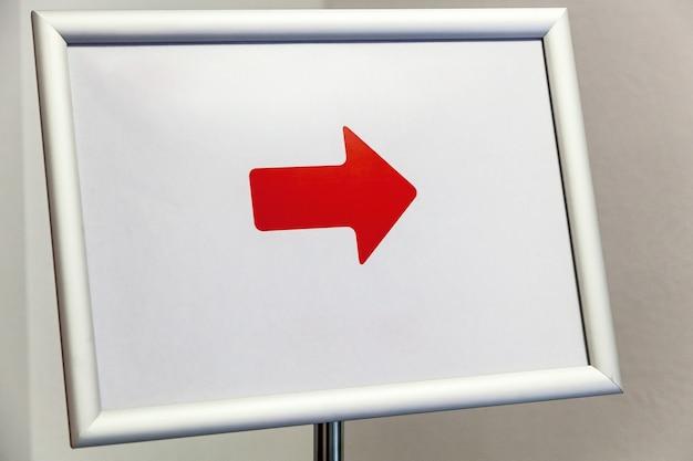 스탠드에 흰색 프레임과 빨간색 화살표가 있는 보드.