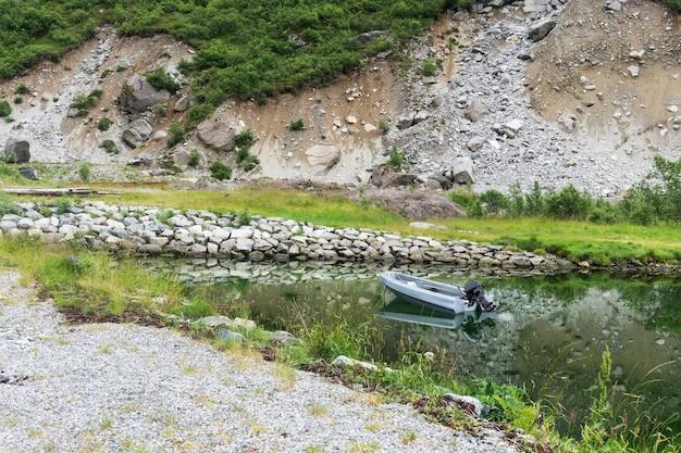 보트와 그림 같은 바위는 맑은 물, lofoten 군도, nordland 카운티, 노르웨이에 반영됩니다.
