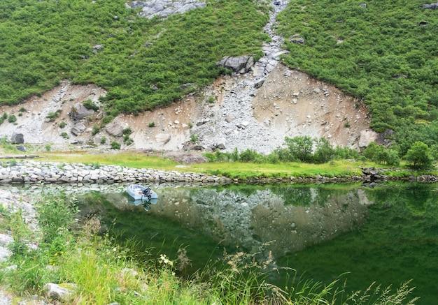 ボートと絵のように美しい岩は、ノルウェー、ノードランド郡、ロフォーテン諸島の澄んだ水に映っています。