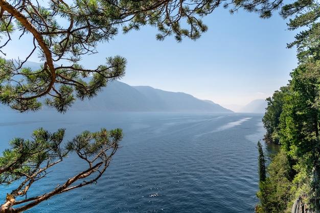Лодка идет по горному озеру. красивое озеро в горах. кедровые ветви нависают над озером. путешествия