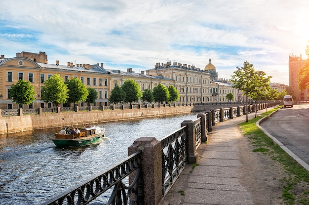 Лодка плывет по мойке в санкт-петербурге в сторону исаакиевского собора ранним солнечным утром.