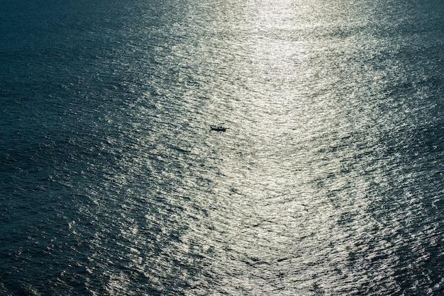Лодка плывет на закате в океане.