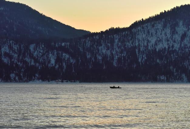 Катер плывет в водах телецкого озера, которое зимой не замерзает