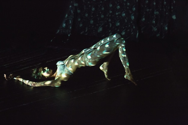 Тело обнаженной женщины с цветным узором в лучевом проекторе