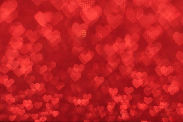 赤い背景にたくさんの小さなハートの形をしたボケ味のテクスチャ。バレンタインデーのコンセプト。