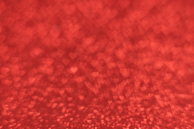 赤い背景にたくさんの小さなハートの形をしたボケ味のテクスチャ。