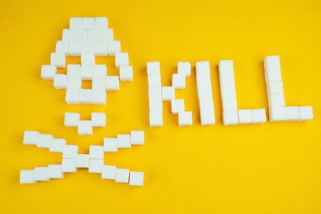 Кости черепа из кубиков сахара на желтом фоне. сахар убивает и концепция диабета. слово убивать от сахара