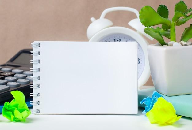 本、手紙の付属品、電卓、目覚まし時計、黄色の背景にリンゴ Premium写真