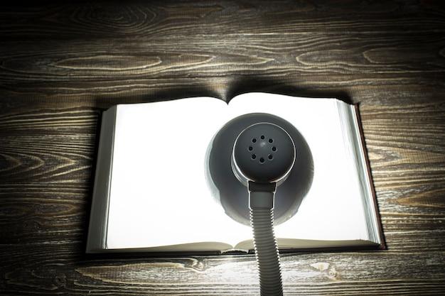 本は暗い部屋のテーブルのランプからの光で照らされています