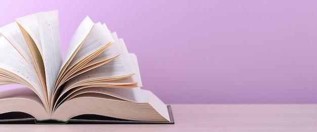 本は開いており、テーブルの上に横たわっていて、シートはピンク色の背景に広げられています。