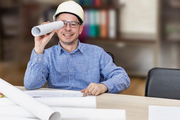 프로젝트 문서와 함께 탁자에 있는 건설 헬멧을 쓴 보스가 겹쳐진 도면을 보고 있습니다. 프로젝트를 성공적으로 완료했습니다. 건축업자, 엔지니어, 머리, 감독.