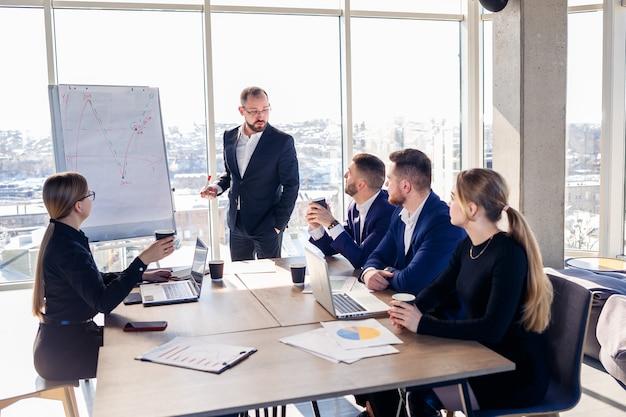 Босс стоит у доски с графиками, демонстрирует статистику, разный персонал, посещающий тренинг, знакомит с новинками компании, отчитывается по результатам работы для партнеров.
