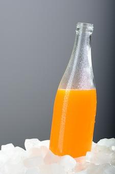 氷の上のオレンジジュースのボトル