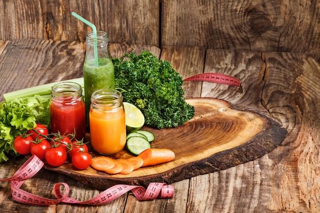 Бутылки со свежими овощными соками на деревянном столе