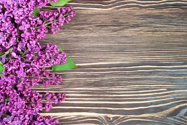 갈색 나무 배경에 라일락 꽃다발. 평면도