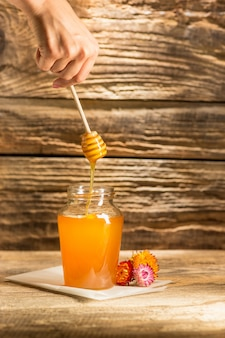 木製のテーブルの上に蜂蜜とボウル。蜂蜜の銀行は木のスプーンの近くに滞在します。