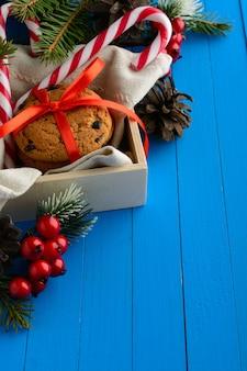 사탕 지팡이와 크리스마스 장식으로 배열 된 초콜릿 쿠키 상자.
