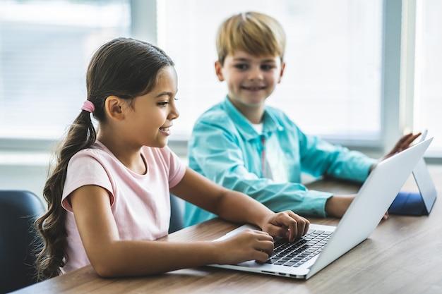 Мальчик и девочка с ноутбуком сидят за столом