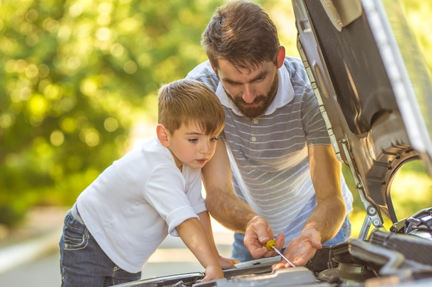 Мальчик и отец проверяют уровень масла в машине