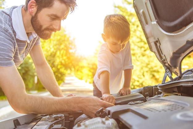 Мальчик и отец ремонтируют машину
