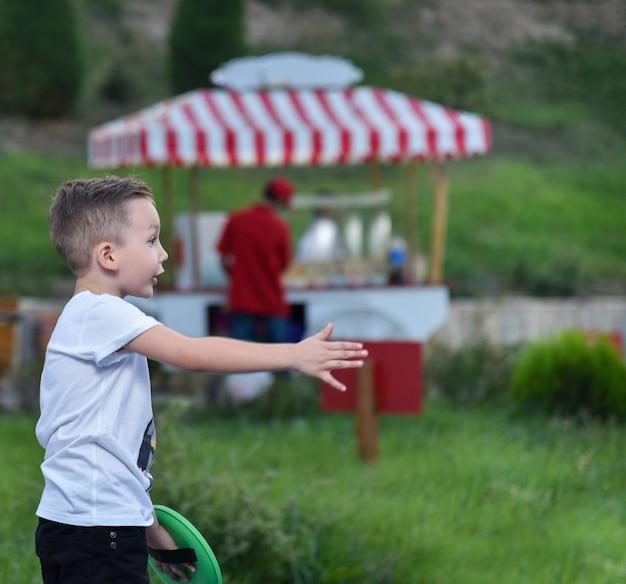 公園の少年がボールを投げる手を引っ張った、ゲーム-プレートでボールをキャッチ