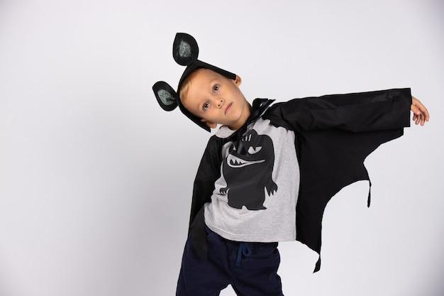 Мальчик-летучая мышь улыбается и счастливо готовится к празднику. фото на белой стене. счастливого хэллоуина.