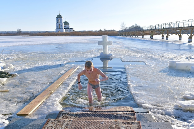 Мальчик купается в холодной воде. крещение. купание в яме.