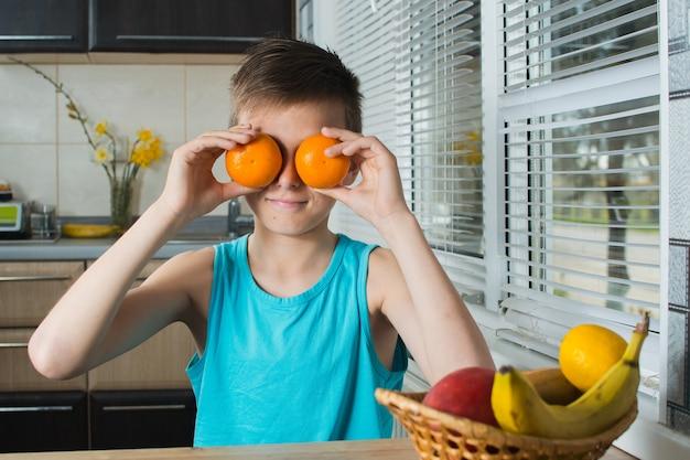 Парень закрывает глаза мандаринами на кухне молодой красотке