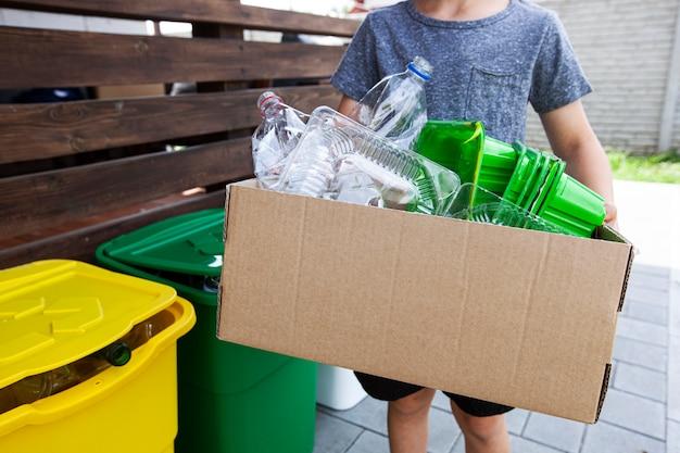 소년은 재활용을 위해 플라스틱 쓰레기를 종이 상자에 수집합니다