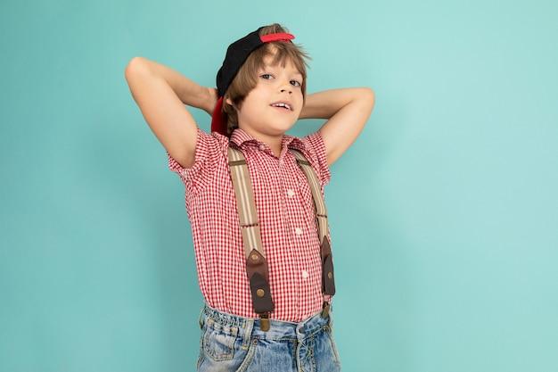 소년은 그의 가슴에 손을 넘어 벽에 단단히 서서 파란색 배경에 고립 된 휴식