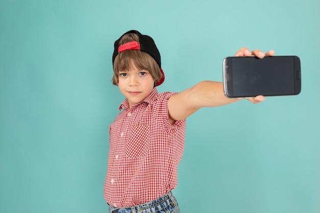 소년은 그의 가슴에 손을 넘어 벽에 단단히 서서 파란색 배경에 고립 된 그의 새로운 전화를 보여