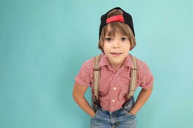 소년은 그의 가슴에 손을 넘어 벽에 단단히 서서 그의 주머니에 손을 유지하고 파란색 배경에 고립 된 미소