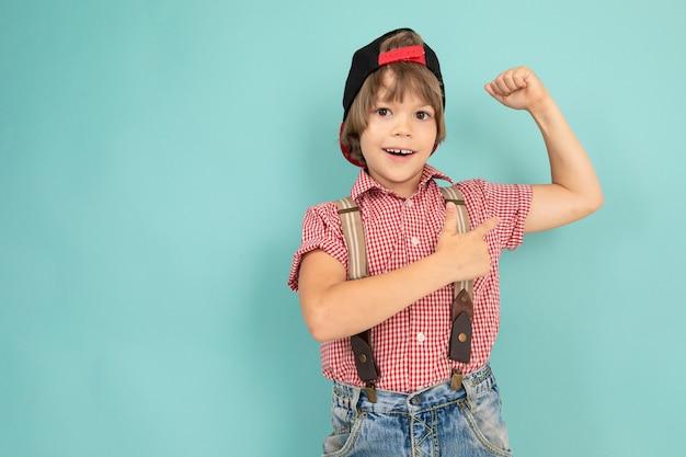 소년은 자신의 가슴에 손을 교차 벽에 단단히 기대어 파란색 배경에 고립 된 그의 근육을 보여줍니다