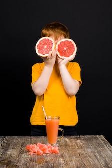 少年は赤いグレープフルーツから苦味と酸っぱいジュースを飲みます