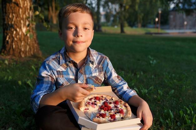 Мальчик съел кусок пиццы.