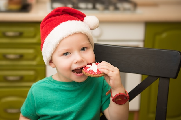 Мальчик ест печенье в шапке деда мороза, сидя на кухне