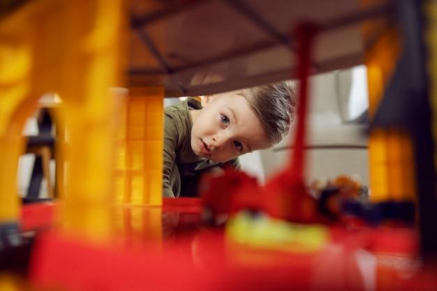 소년은 놀면서 탐색합니다. 실내에서 장난감을 가지고 노는 아기의 사진. 유치원에서의 행복한 어린 시절, 아동 발달. 어린이집 어린이 교육, 게임과 성장