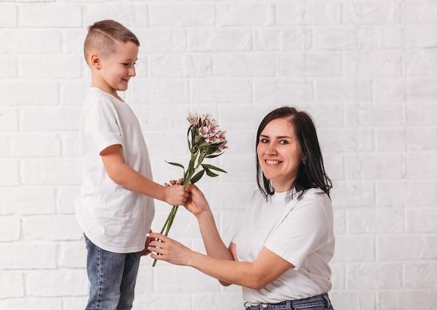 Мальчик дарит цветы своей матери на белой поверхности. поздравления