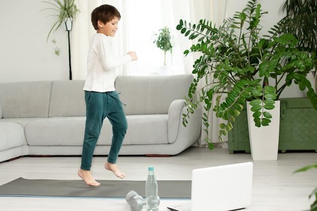 소년은 온라인으로 집에서 스포츠를 즐깁니다. 아이는 방에서 운동을합니다.