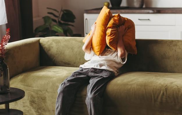 その少年は枕に顔を隠している。ティーンエイジャーはソファに座って悲しいです。怒りと失望