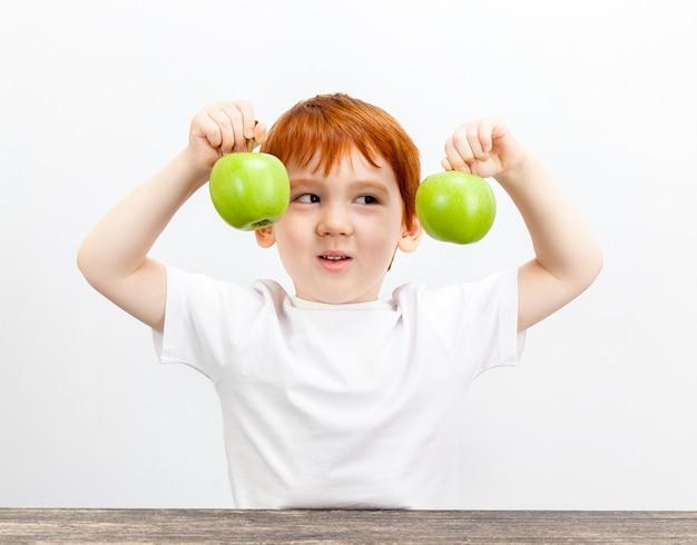 소년은 손에 녹색 사과를 들고 미소로 사과를보고 소년은 빨간 머리를 가지고 있습니다.