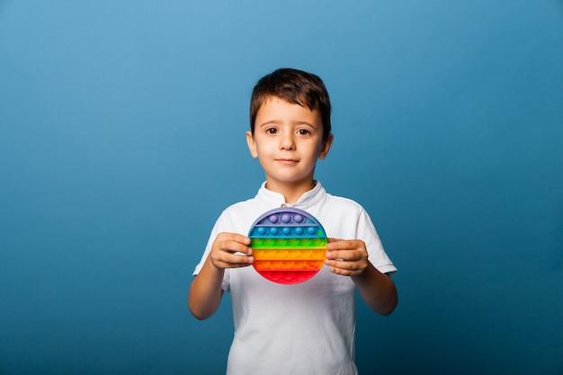 Мальчик держит в руках игрушки, которые хлопают в ладоши. пуш игры. счастливый мальчик с поп.