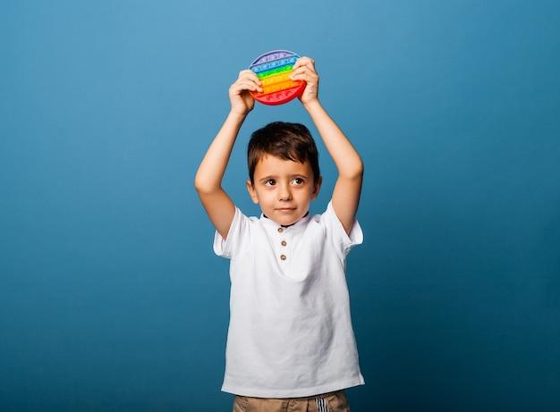Мальчик держит в руках хлопающие игрушки. пуш игры. счастливый мальчик с поп.